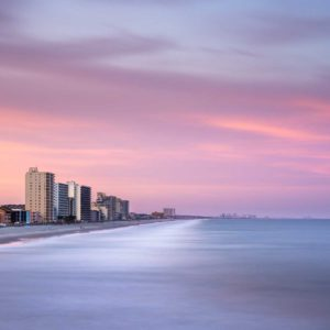 art print of the Garden City shore line in South Carolina, showing a line of highrises with deep sunset colors in the background