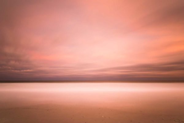 wide view of the ocean with beach in the foreground, orange sunset clouds creating an abstract view by the long exposure effect