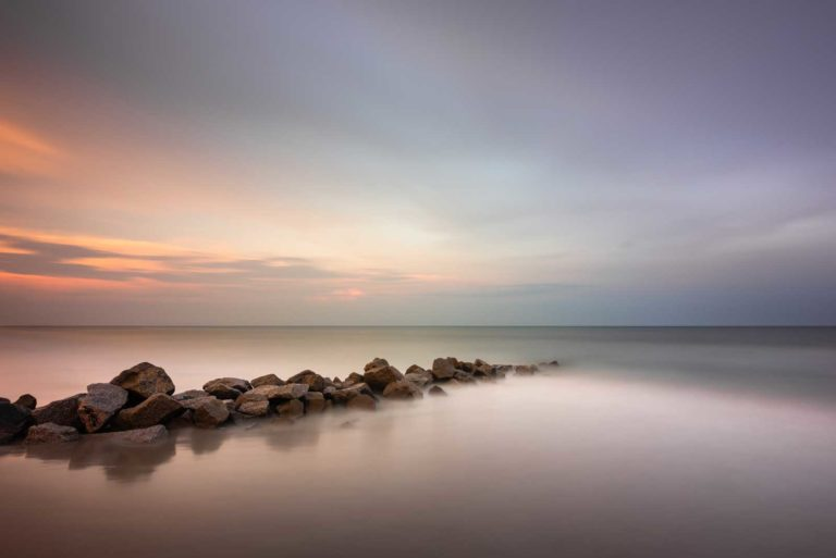 art print of a rocky groin lighted by moody sunset colors, with a wide view of the ocean, created with a long exposure technique