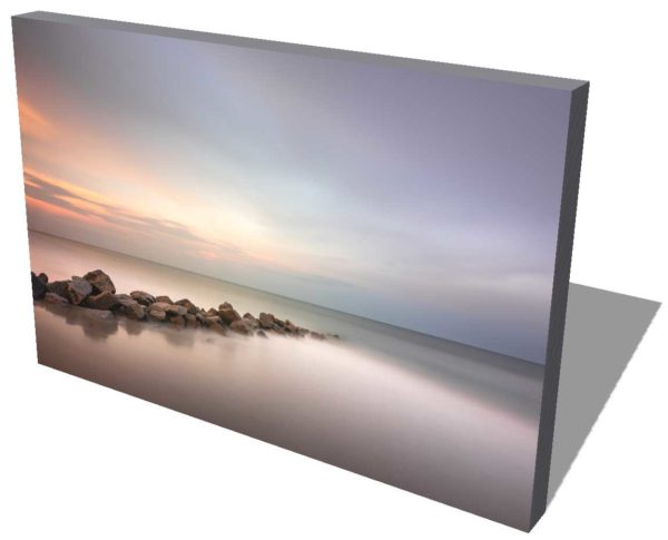 canvas print of a rocky groin lighted by moody sunset colors, with a wide view of the ocean, created with a long exposure technique