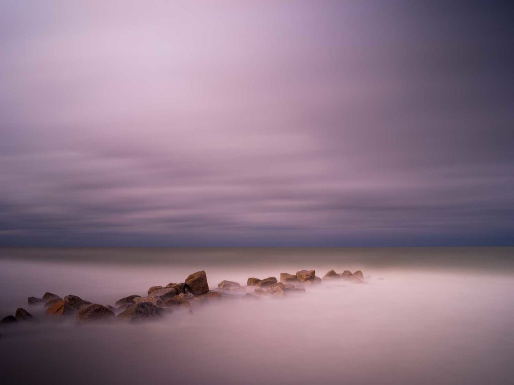 rocky groin with deep purple after sunset colors, an abstract view created by a long exposure photography technique