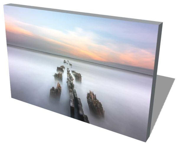 canvas print of a weathered groin on folly beach, south carolina, with orange and yellow sunset colors, in the background