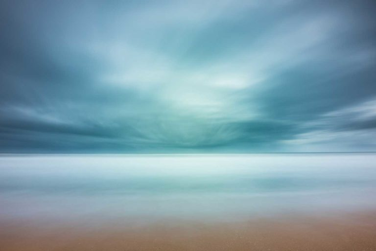 wide view of the ocean with beach in the foreground, blue strormy cloud cover creating an abstract view by the long exposure effect
