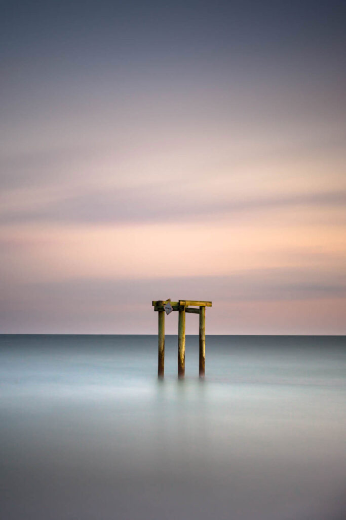 Groin during sunset, a minimalist view created by a long exposure photography technique by Ivo Kerssemakerws