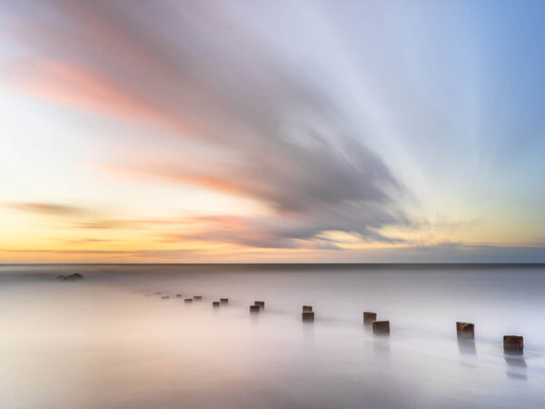 weathered groin on folly beach, South Carolina at sunrise, colorful cloud movement in the background,, art photography
